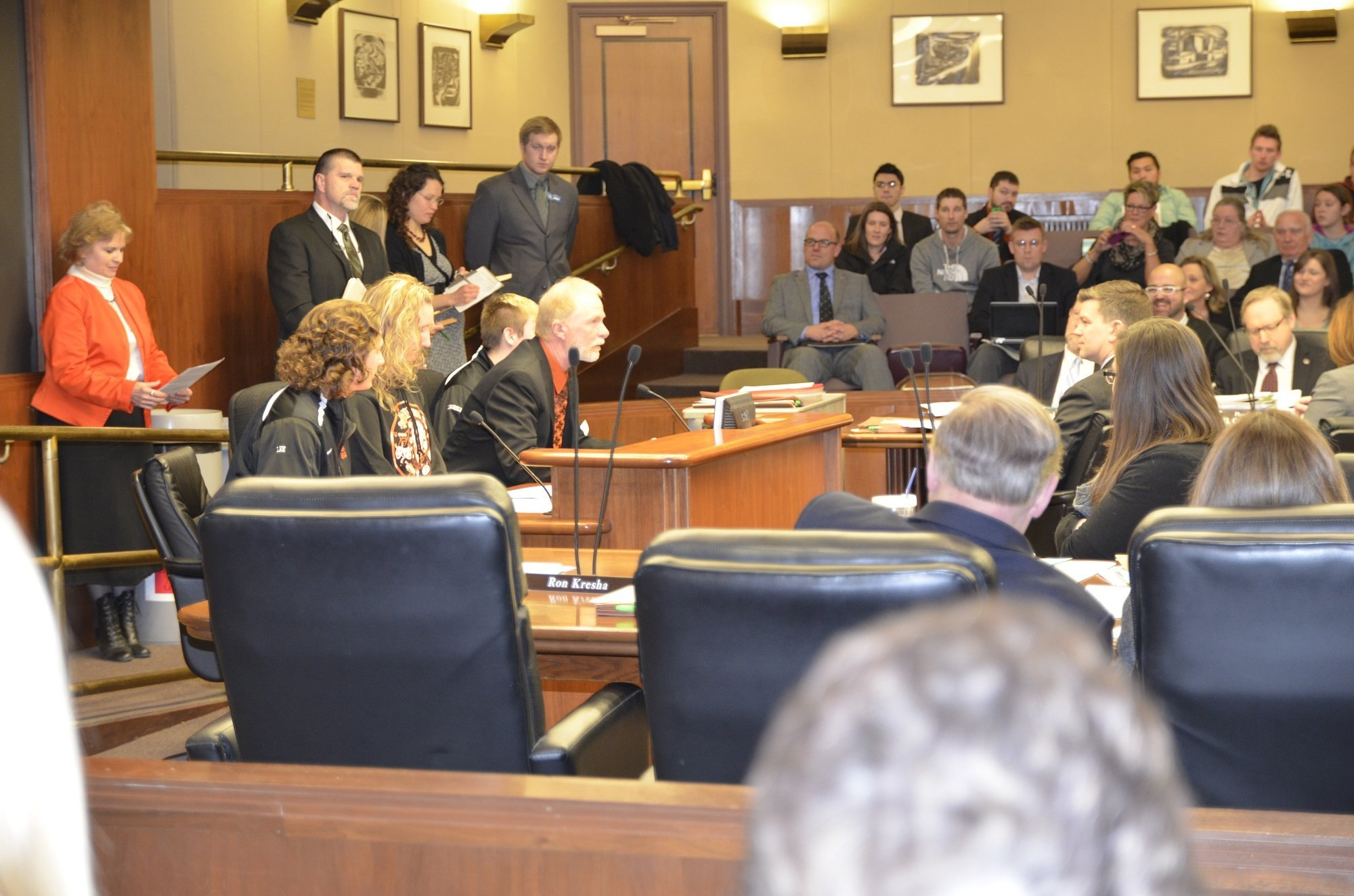 Ogilvie School Board Chair Jeff DeYoung (sitting front) and Ogilvie Superintendent Kathy Belsheim (standing, rear) and other school officials urged committee members to let them maintain their four-day school week schedules.
